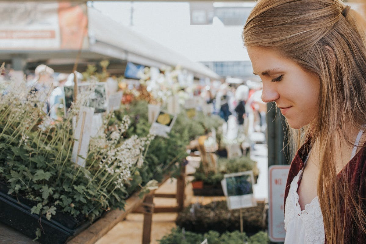 A woman browses in a marketplace of plants.