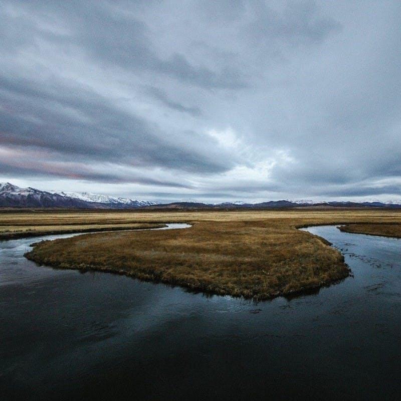 A river snaking through a tundra's grassland.