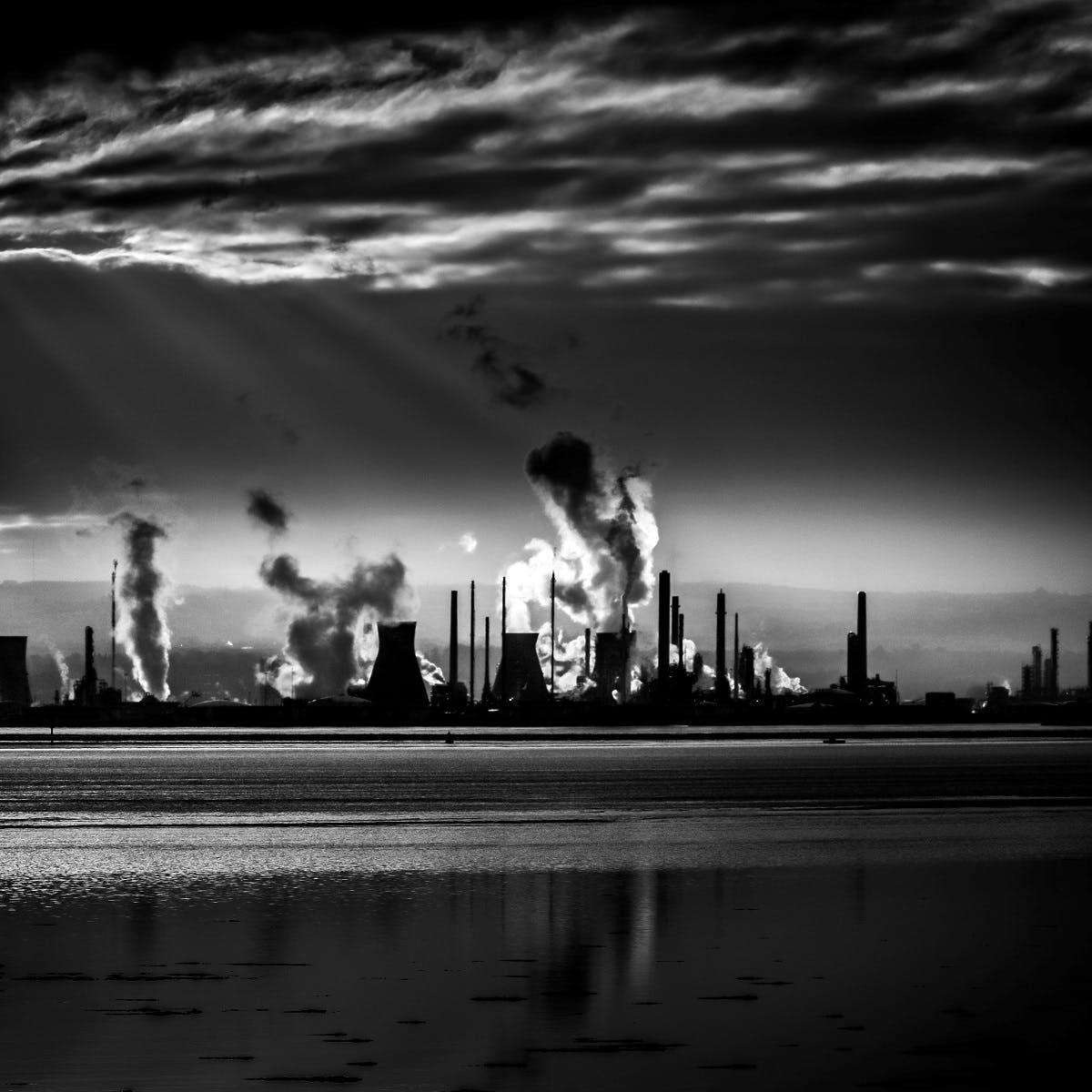 An industrial city on the horizon with a number of factories pumping pollutants into the atmosphere