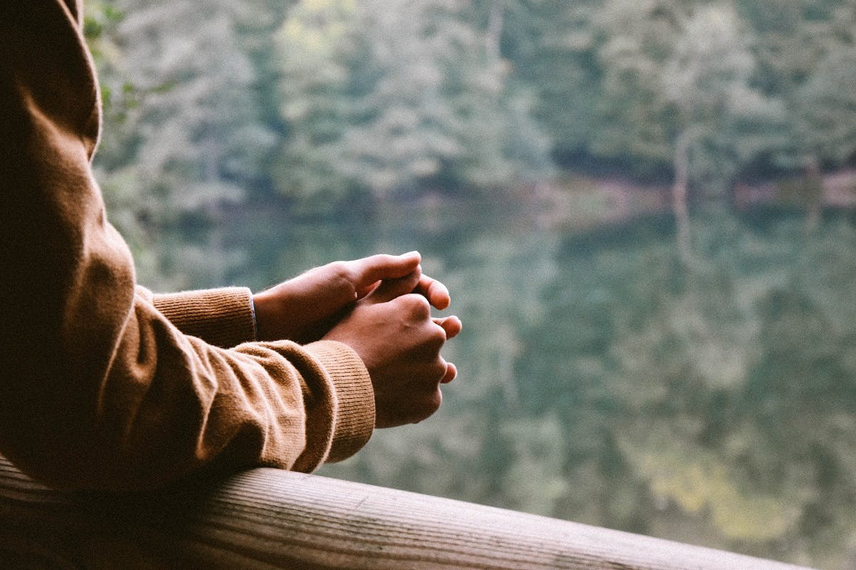 A person pausing for thought on a bridge overlooking a lake and trees. Taking time out each day to pause and collect your thoughts, even if 5 minutes, is step closer to Slow Living.