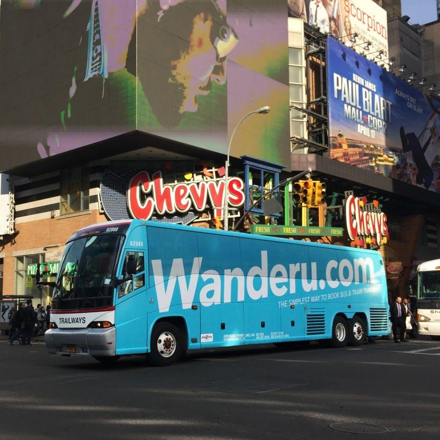 A Wanderu bus passes through a city centre.