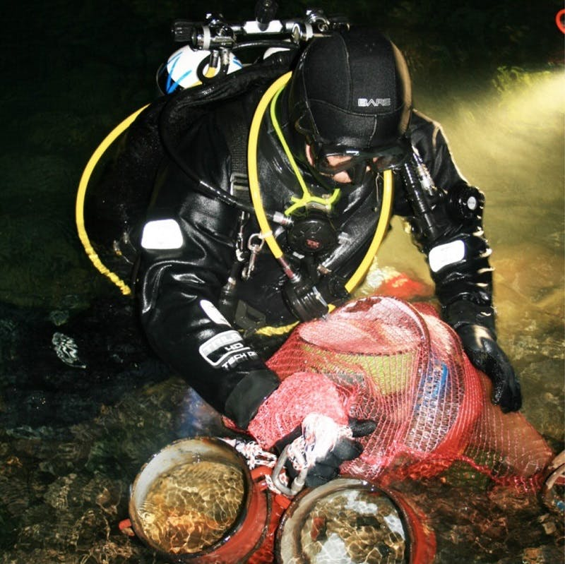 A cave diver partially out of water, with full equipment, putting solid waste into a bag inside a cave. Credit: PROTEUS project team.