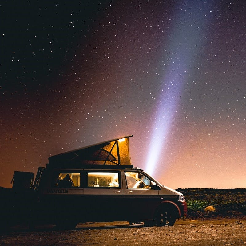 A camper van parked under the stars . Silent star gazing evenings are just one of many advantages to van life.