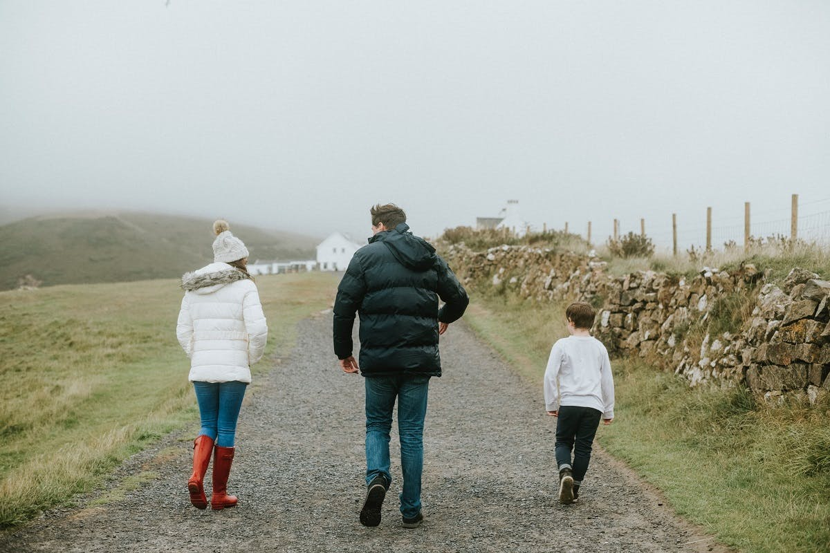 A father walks with his two children through some farmland on a misty day.
