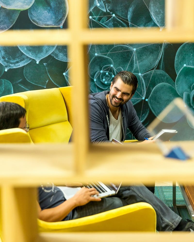 Two office workers happily chat on yellow office sofas.