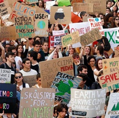 """A group of young people at a climate strike, one holding a sign that reads """"Less is More. It's Eco-Logical"""""""