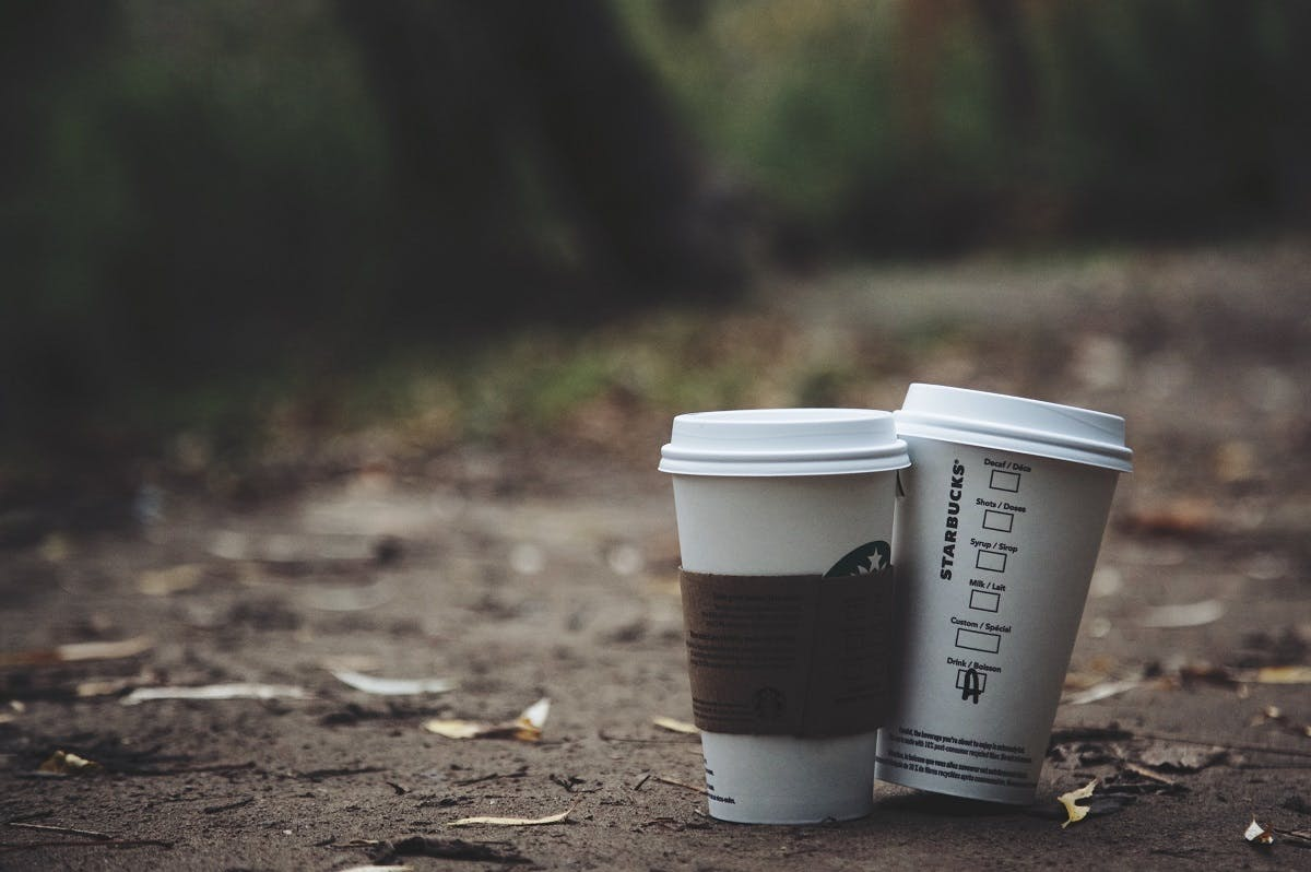 Take away Starbucks's coffee cups left on a table. Investing in a reusable coffee cup is an easy win on living plastic free