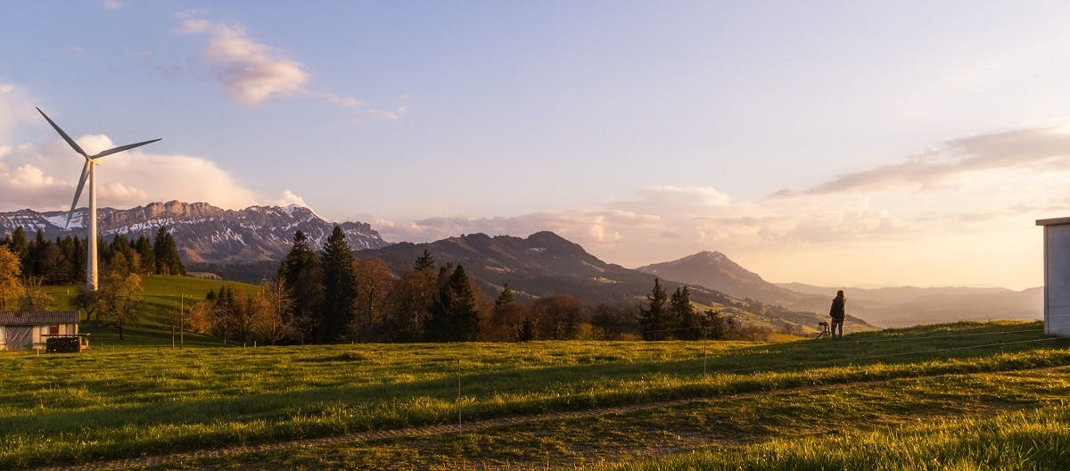A panorama view of mountains, forest, fields and a green energy wind turbine