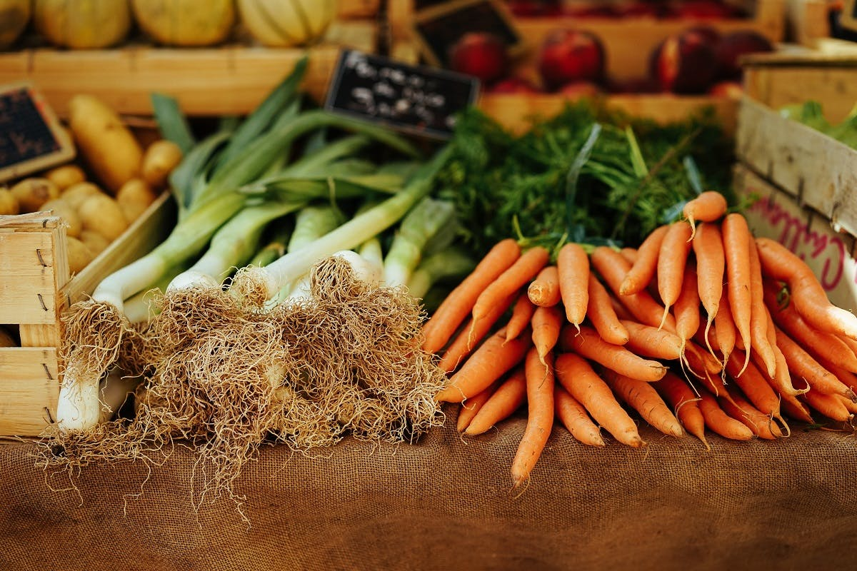 Organic leaks and carrots on sale at a farmers' market. To eat seasonally and locally helps your local farmer.