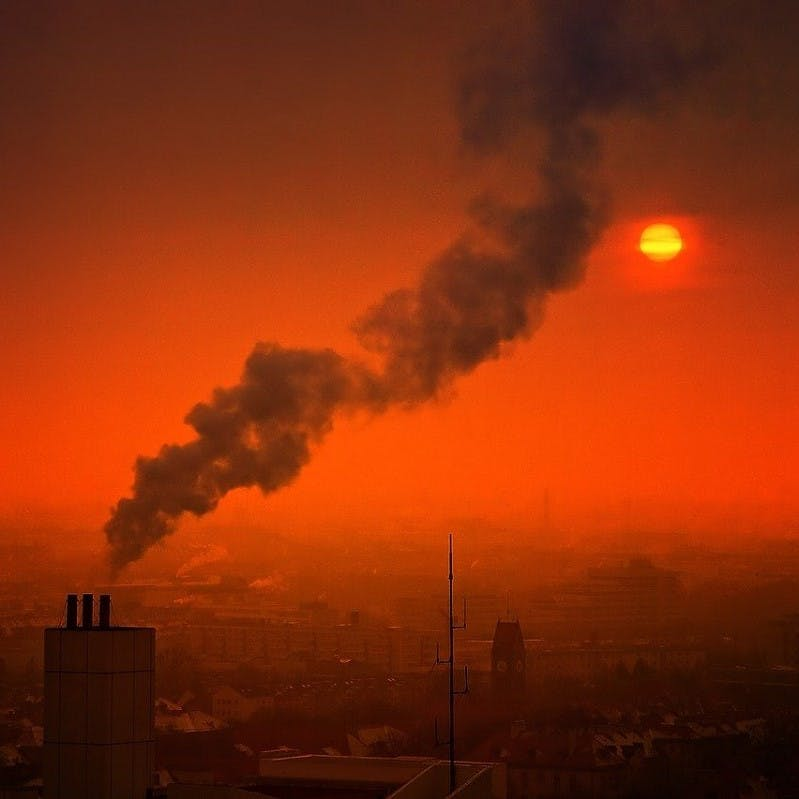 A fume of smoke rises into the air in a polluted city.