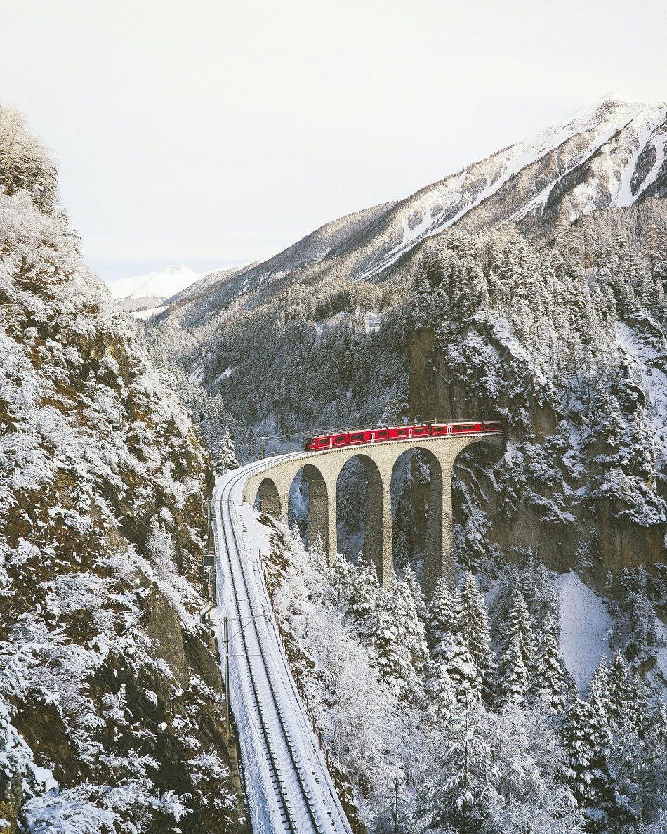A train passes through a tunnel in the snowy Swiss Alps.