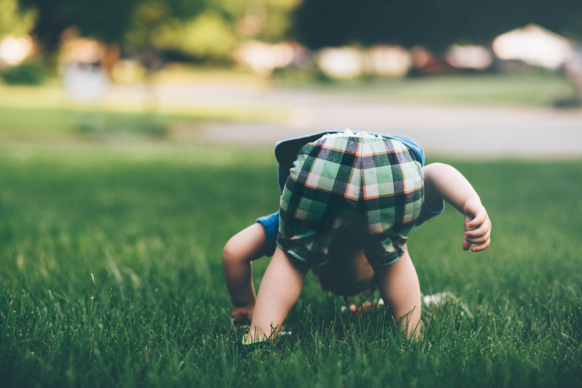 A toddler playing in the grass outside. Regular time in nature is a must when raising an eco baby.