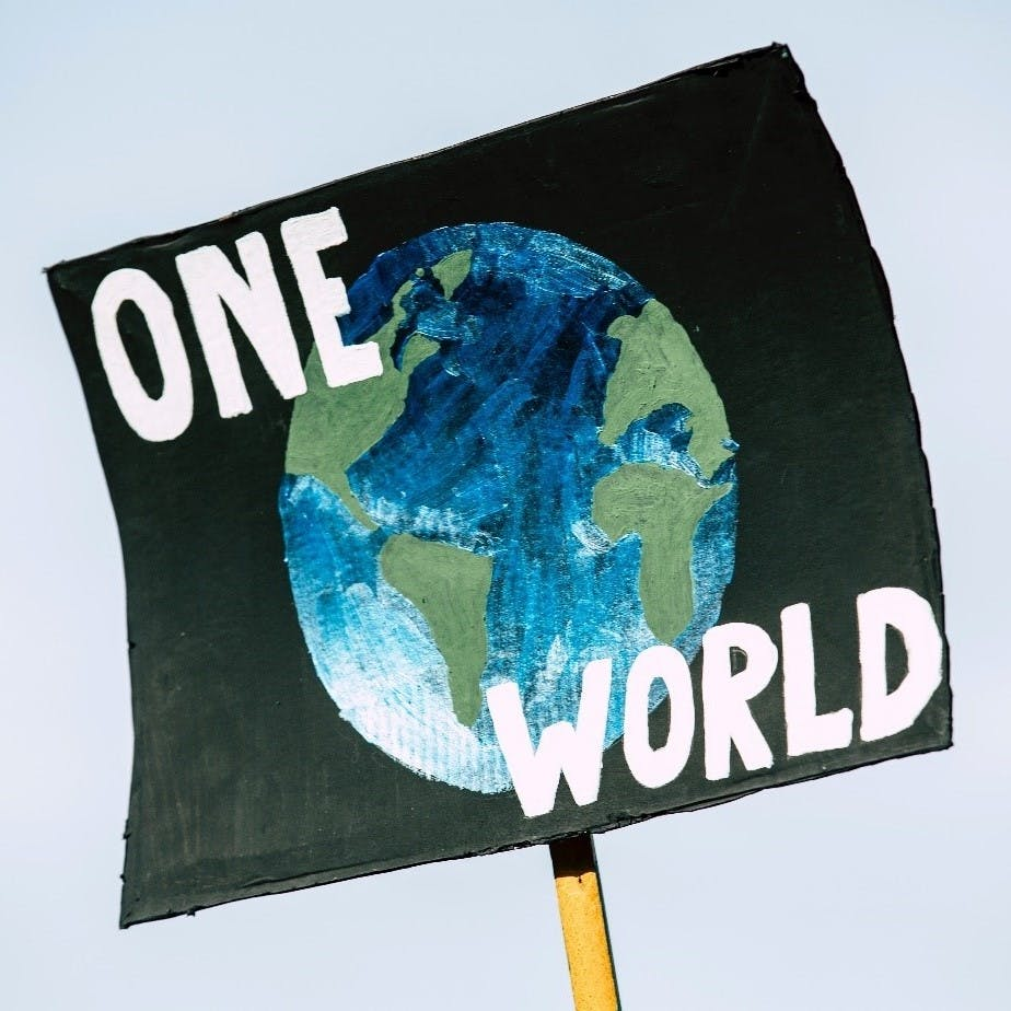 """A """"One World"""" poster at a climate change strike."""