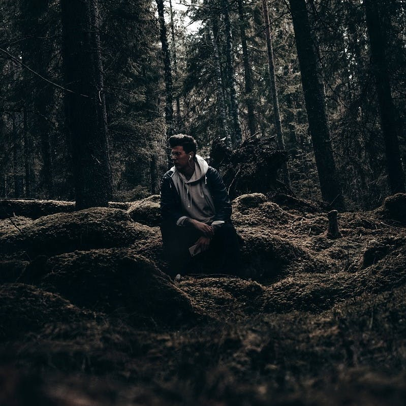 A man listening to a rewilding podcast in the woods