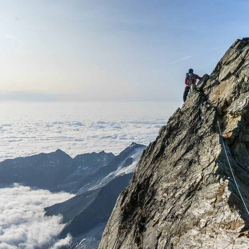 Upon a mountain above the clouds, a rock climber is seen.