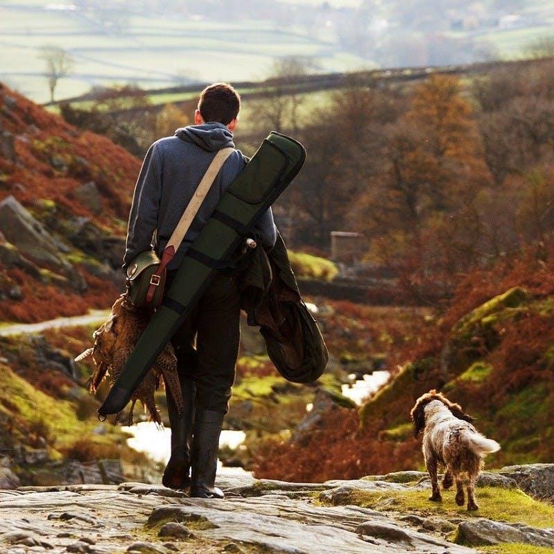 A gamebird hunter walks down a rural path along side his dog.