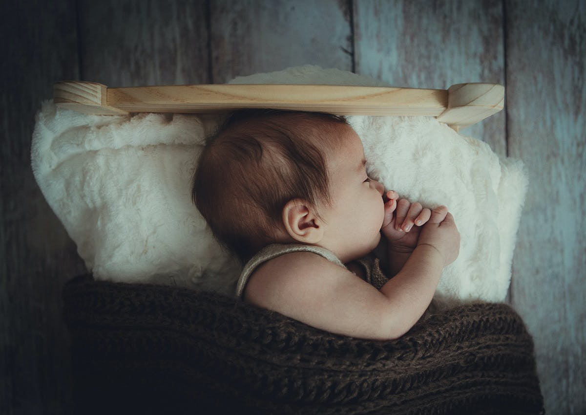 An eco baby sleeping in its hand built cot and knitted blanket