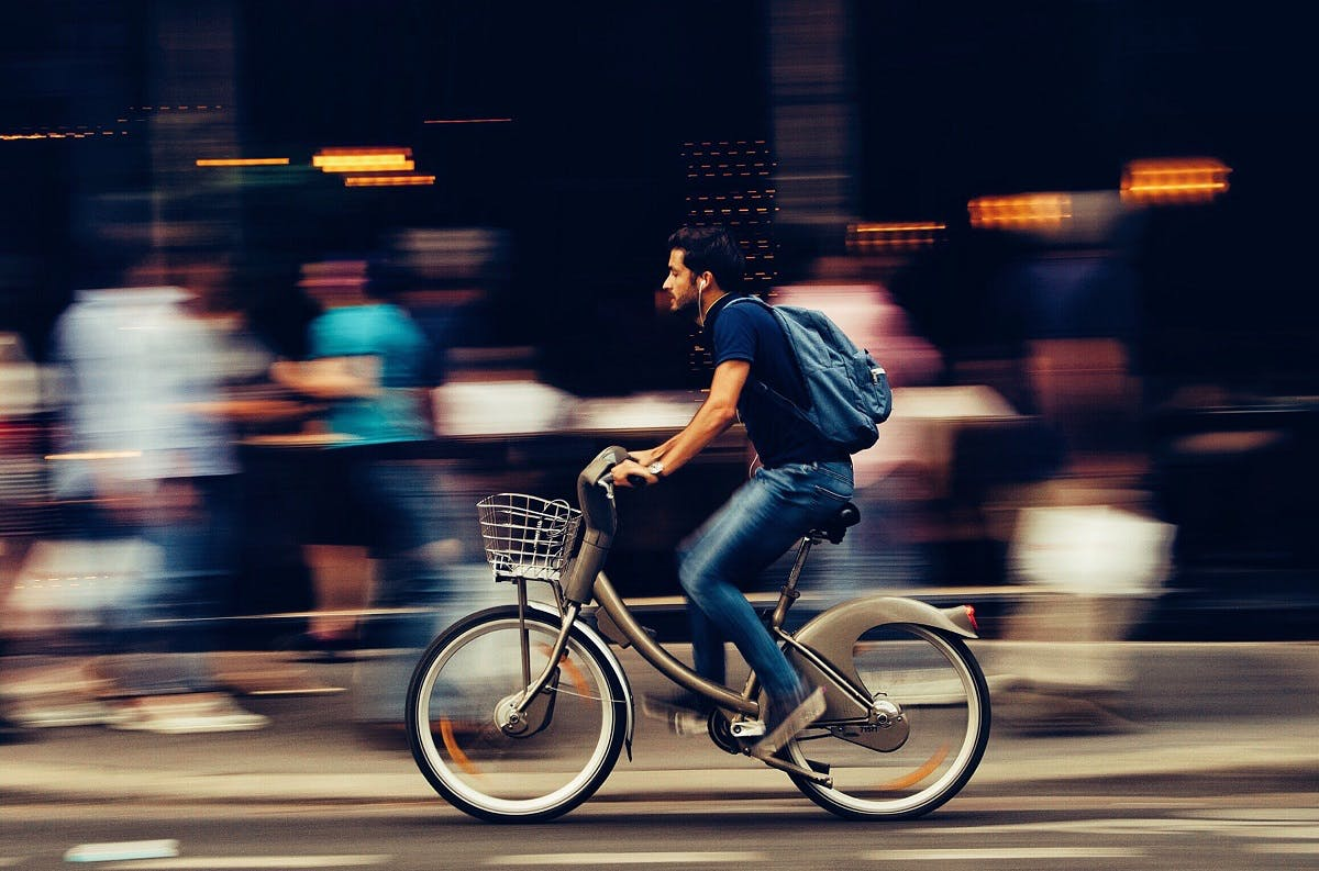 A man cycling through the city on an e-bike. E-bikes are at the forefront for the green commute.