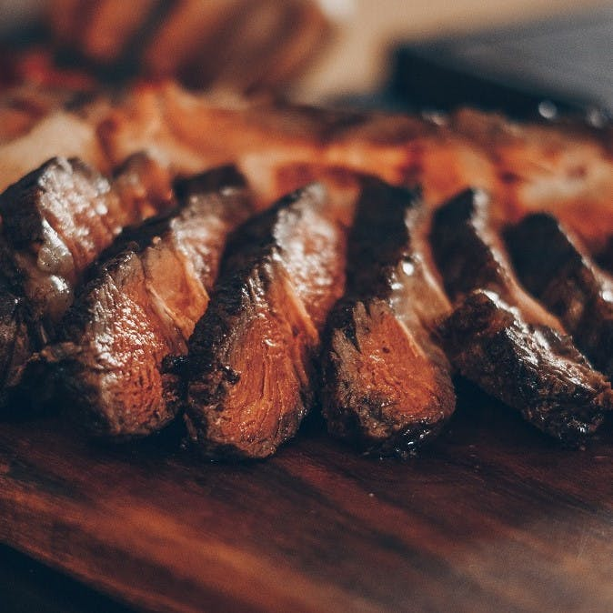 Slices of succulent steak on a wooden serving board. Cutting back on the consumption of such red meat dishes will significantly reduce your CO2 footprint.