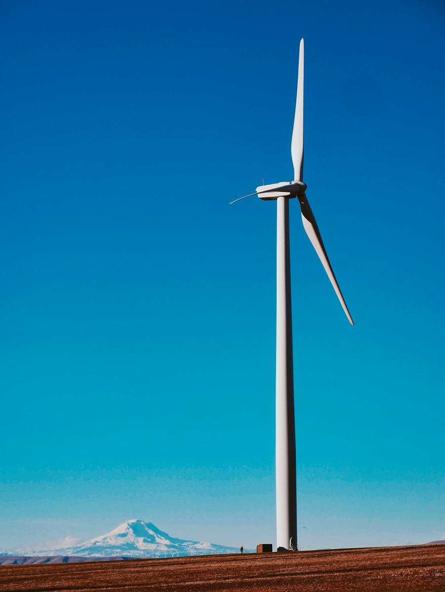 A wind turbine in the mountains. Renewable energies such as wind energy is a prominent strategy in the Paris Agreement and in the fight against climate change.