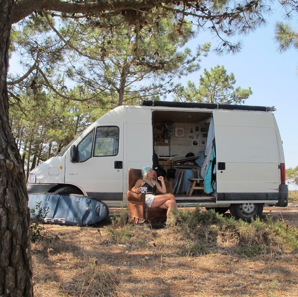 A surfer enjoying van life in the sun in Portugal