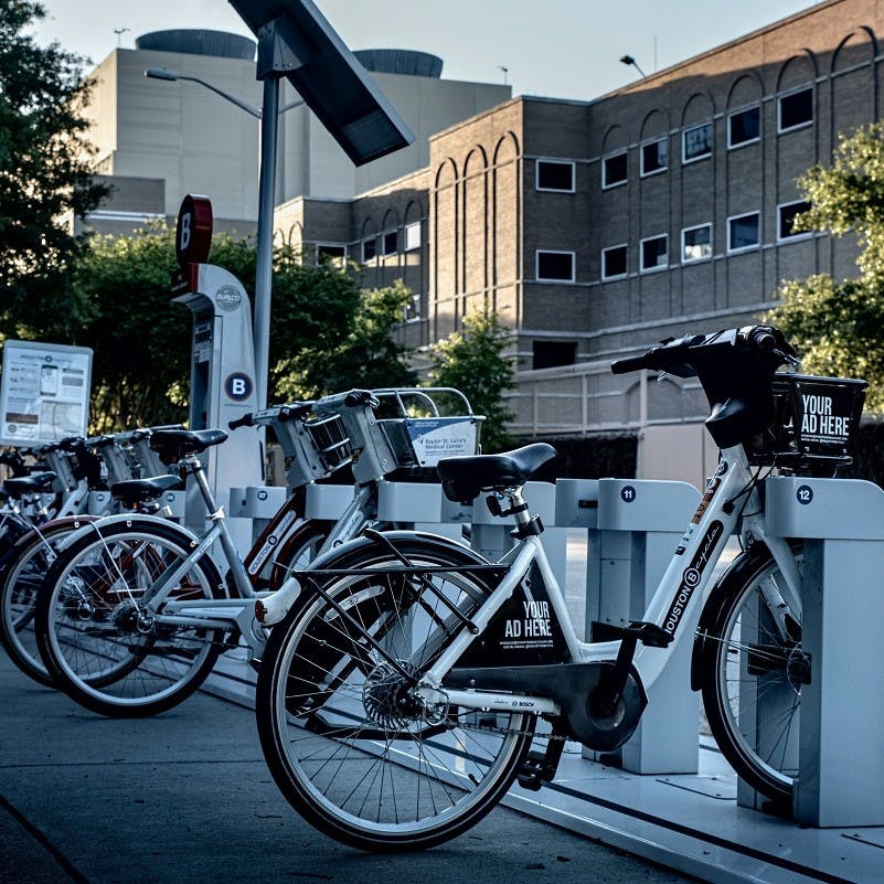 Electric bikes lined up at a charging station outside an office building where employees choose cycle-to-work schemes as perks.