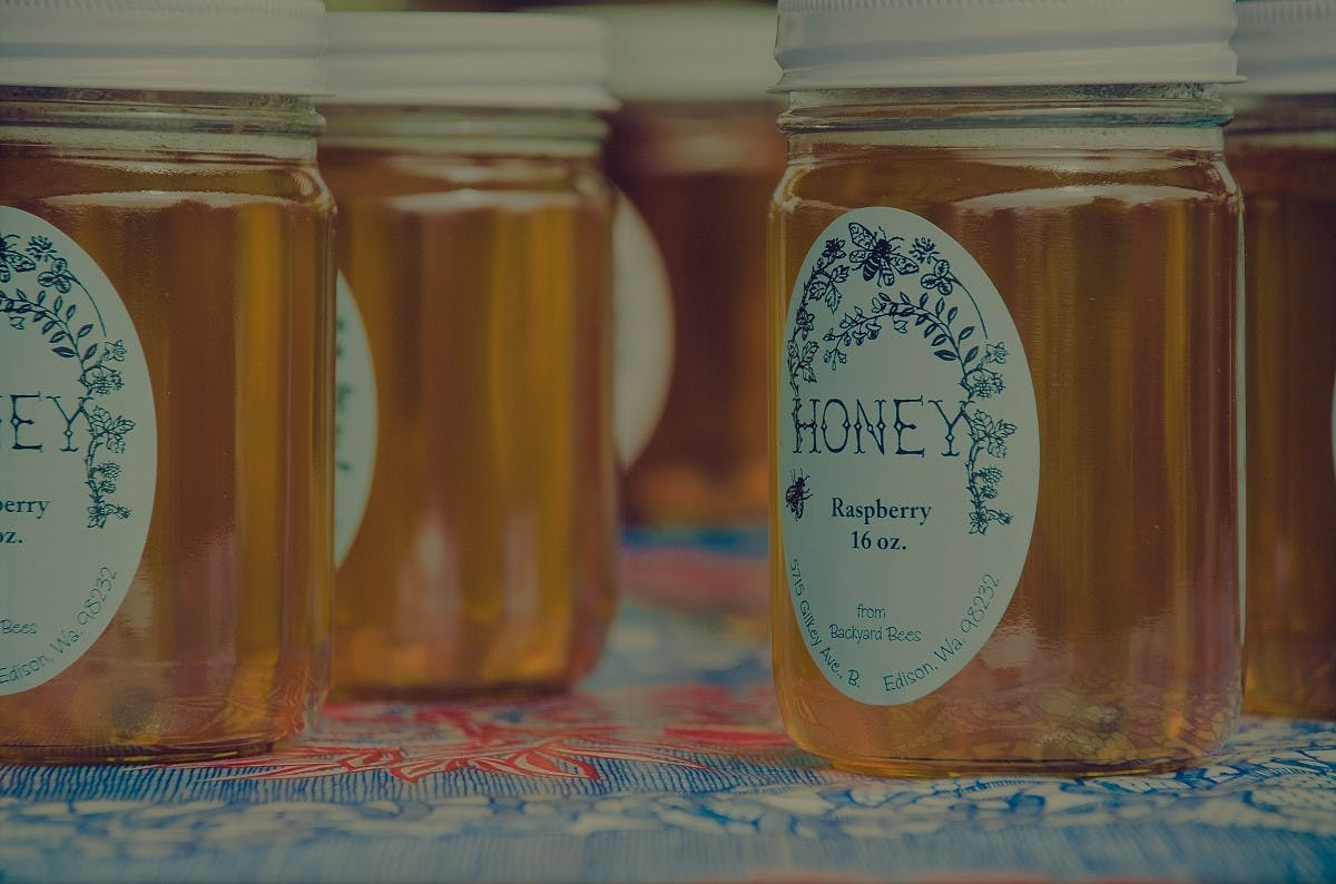 Jars of local raspberry honey on display. Local honey is the epitome of eating seasonally and local.