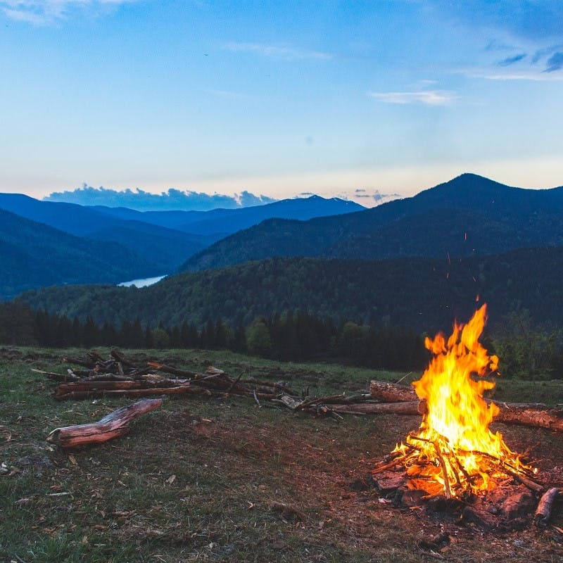 A camp fire with view of lake and mountains. Another great advantage of van life, the adventure!