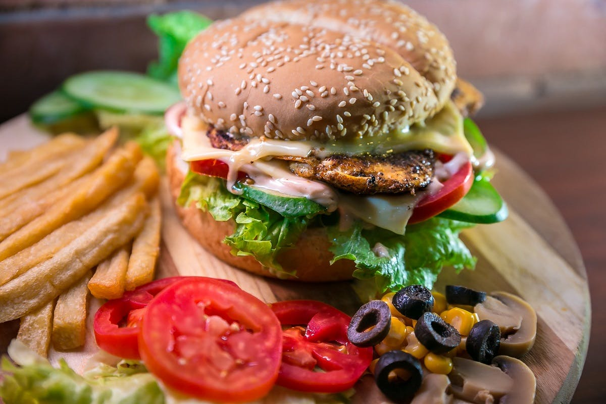 A chicken burger with salad and fries is  an easy white meat dish.