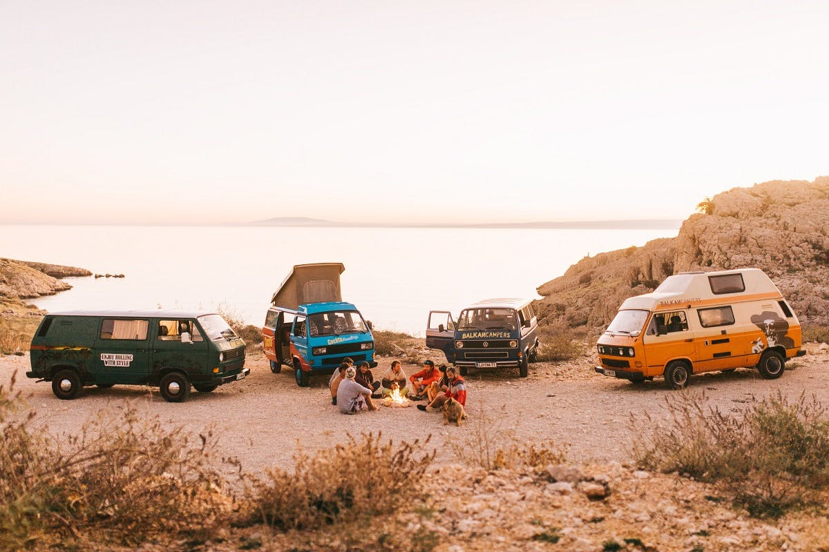 Four camper vans parked up by the beach for a camp fire. #vanlife