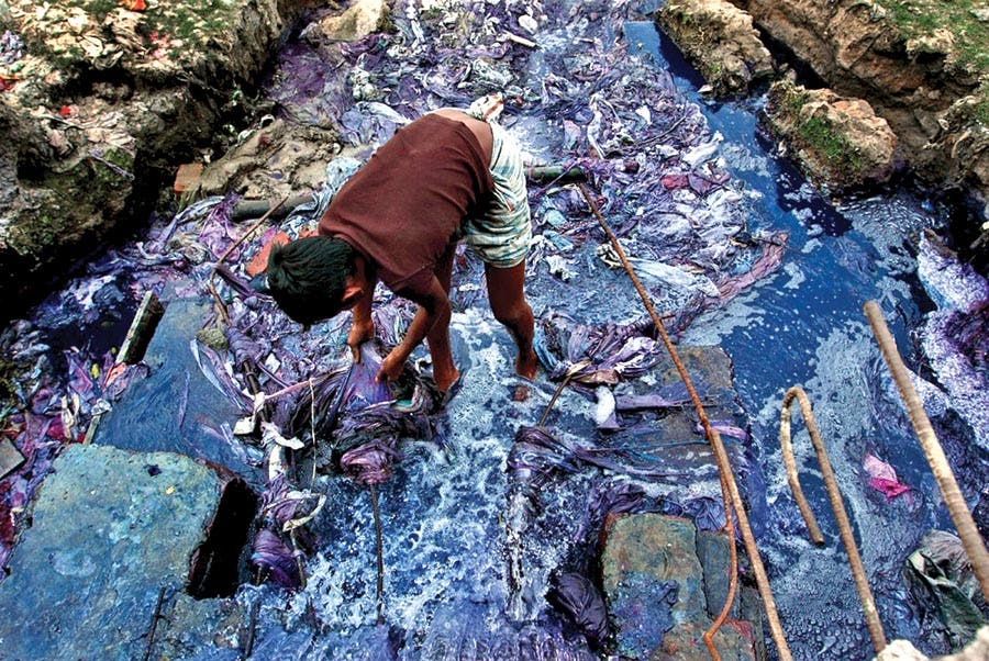 A boy standing in a polluted river caused by the production of fast fashion. Sustainable fashion doe not create such environmental problems.