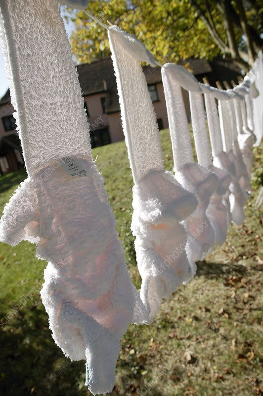 Twelve white cloth nappies hanging on a washing line. Reusable nappies are an easy first step in raising an eco baby.