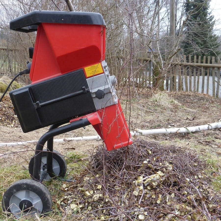 An electric shredder chopping up garden waste
