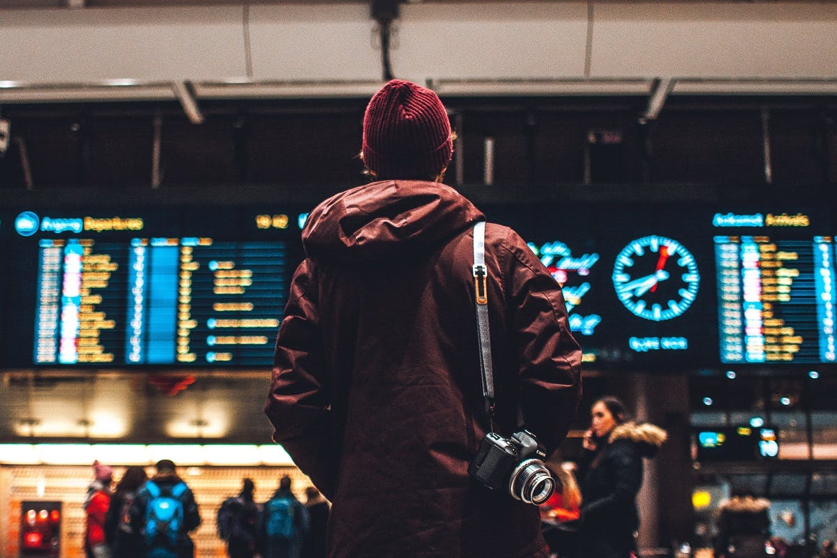 A guy checking the departure boards at the airport