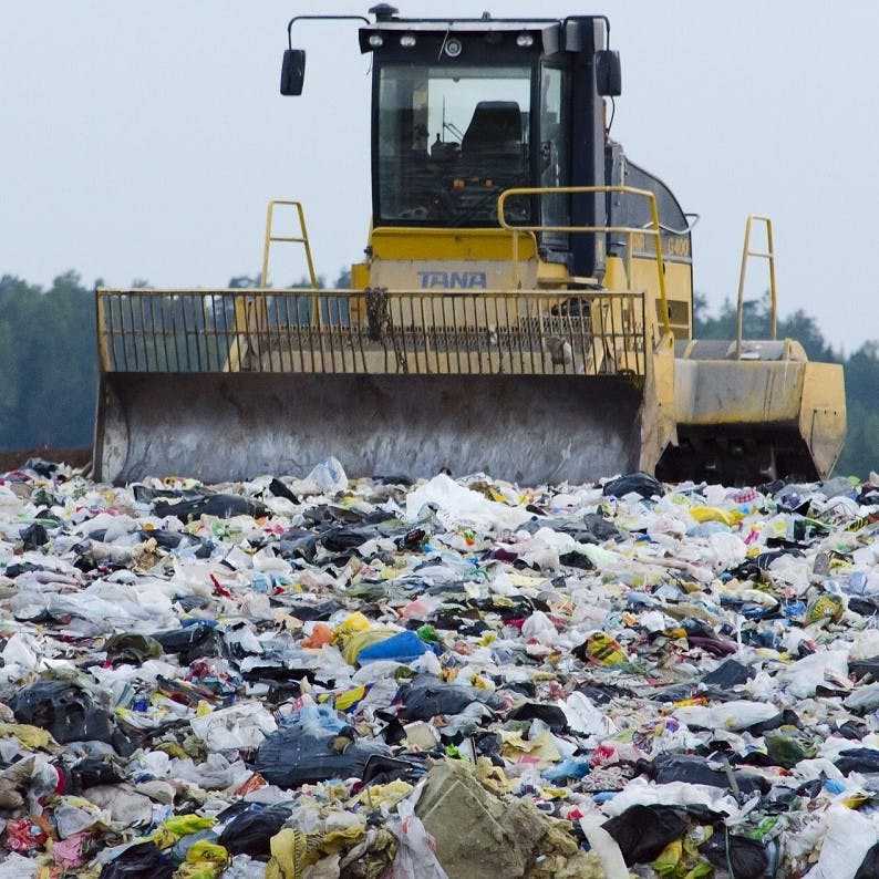 A bulldozer surrounded by waste at al landfill site adjacent to a beautiful forest. Disposable nappies make up for a significant amount of landfill waste.