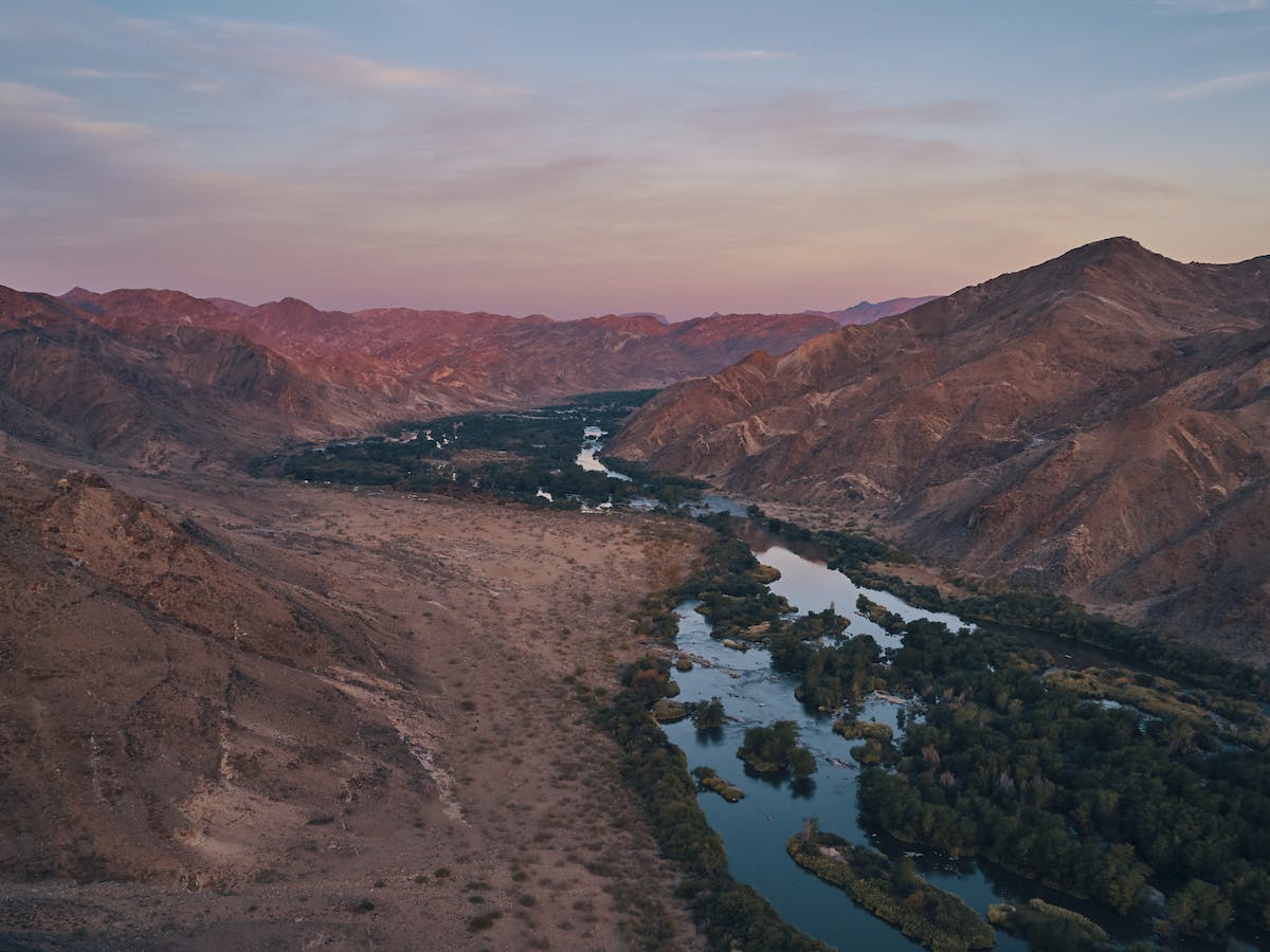A lush river runs through mountains in the centre of the image, with pink sunset hues filling the sky