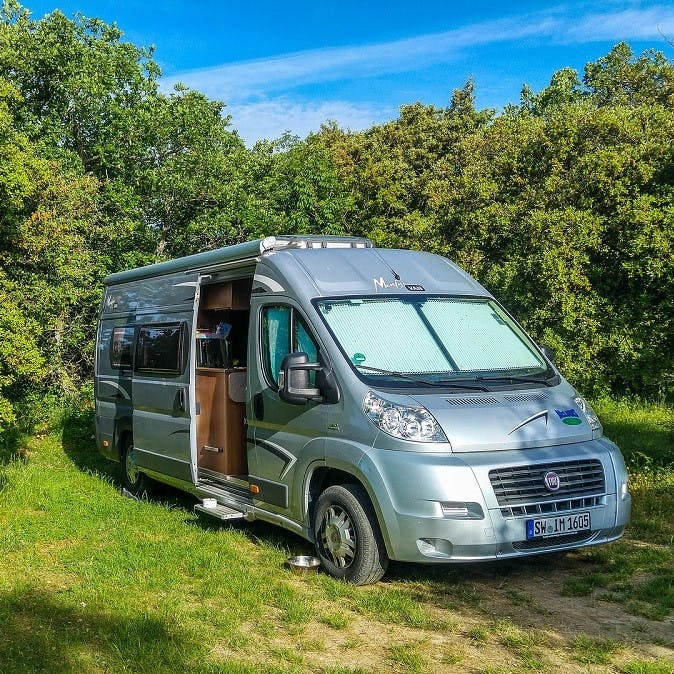 A modern Fiat Ducato camper van parked in a forest
