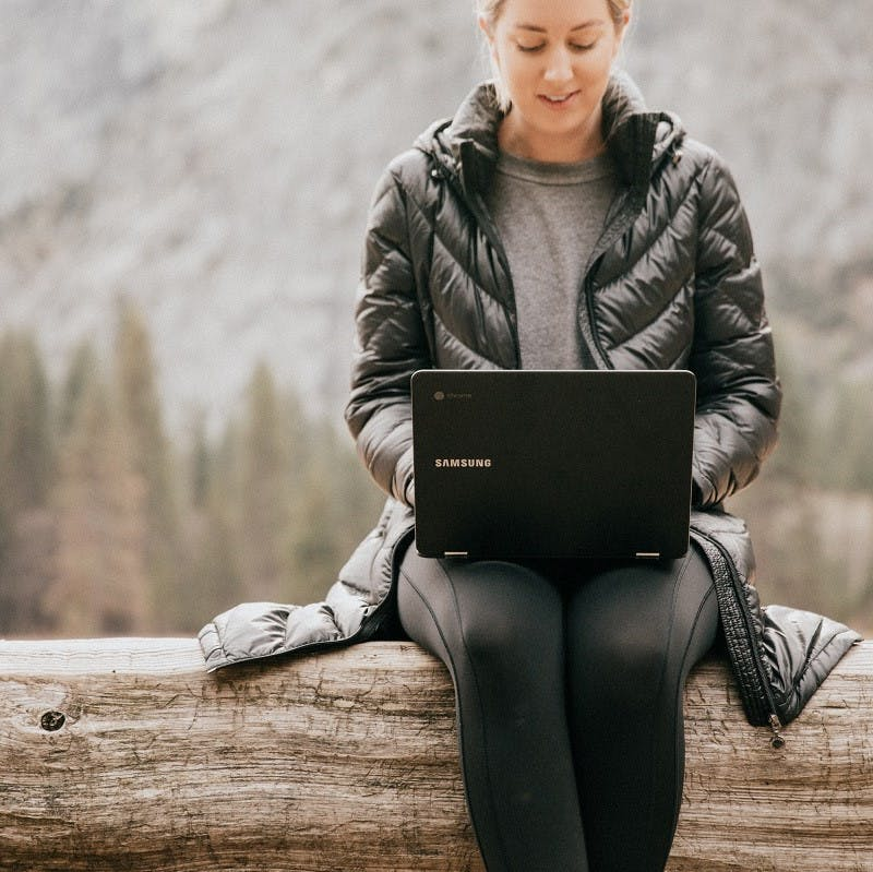 A woman sitting on a log working on her laptop with nature in the background.