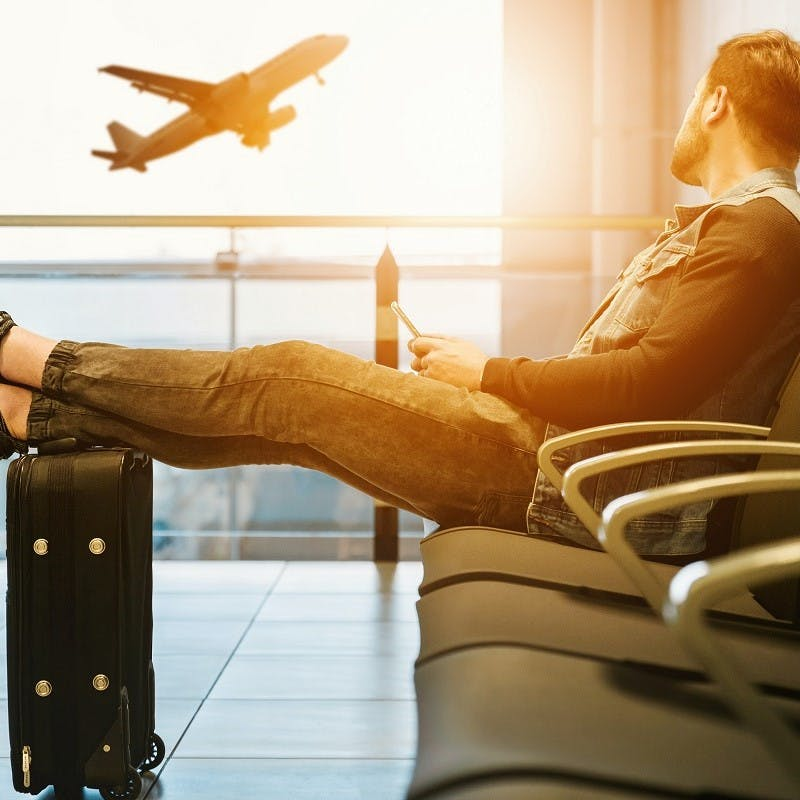 A man waiting in the departures lounge at an airport. An easy tip to sustainable flying is to pack light.