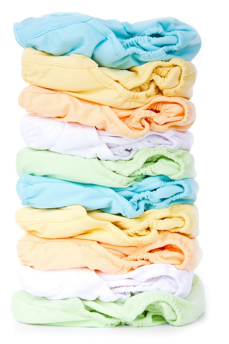 A pile of reusable washable cloth nappies in a variety of colours