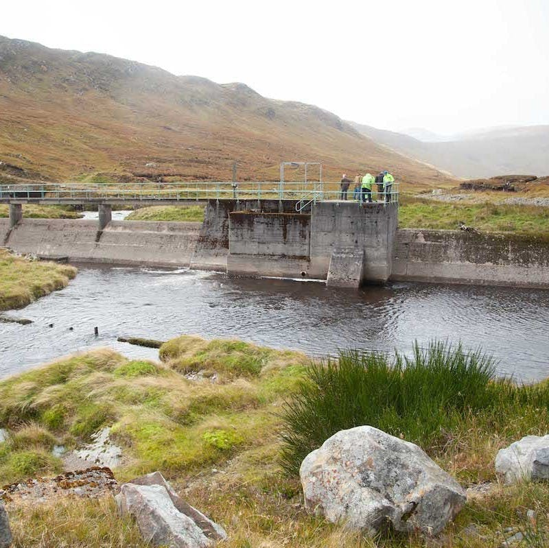 A river and dam on a misty day in Scotland. Dams can cause problems for wild Atlantic salmon migration