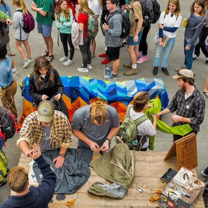 A group of people repairing, reusing and recycling clothing at a Patagonia Worn Wear event