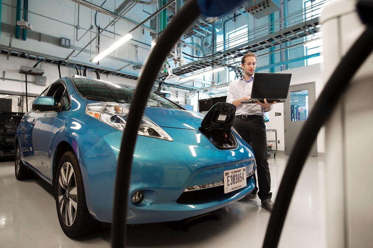 An electric blue electric car being manufactured. The emissions factors of manufacture and battery disposal vs lifetime use of an electric  car is a heatedly debated topic regarding electric cars pros and cons.