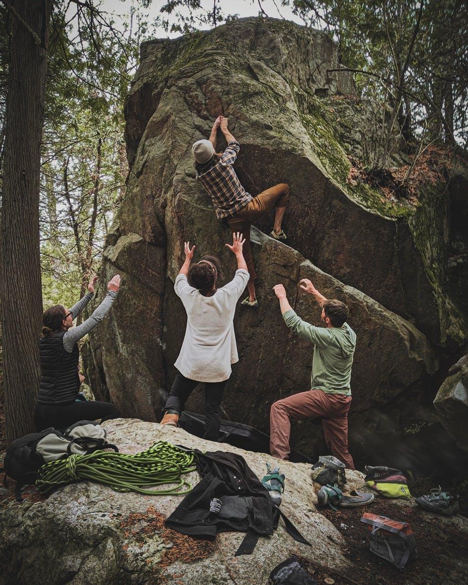 A group of climbers help a novice climber up a boulder.