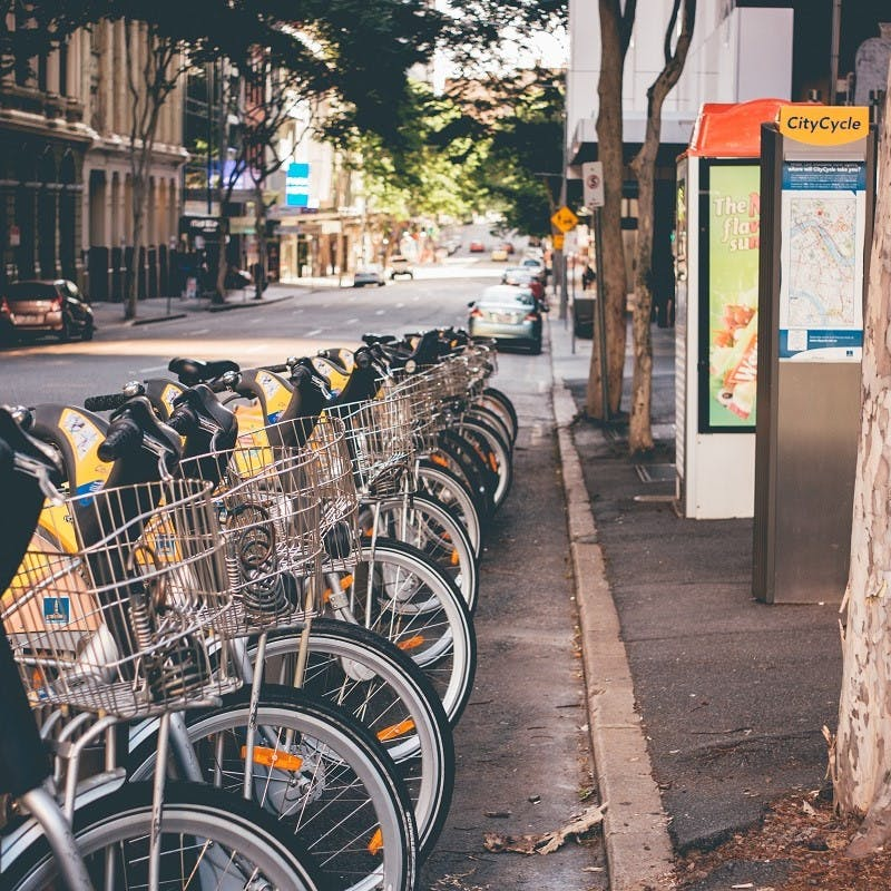 A row of e-bikes lined up along a city's sidewalk. With all modern cities offering e-bikes, the idea of a green commute is that much more realistic.