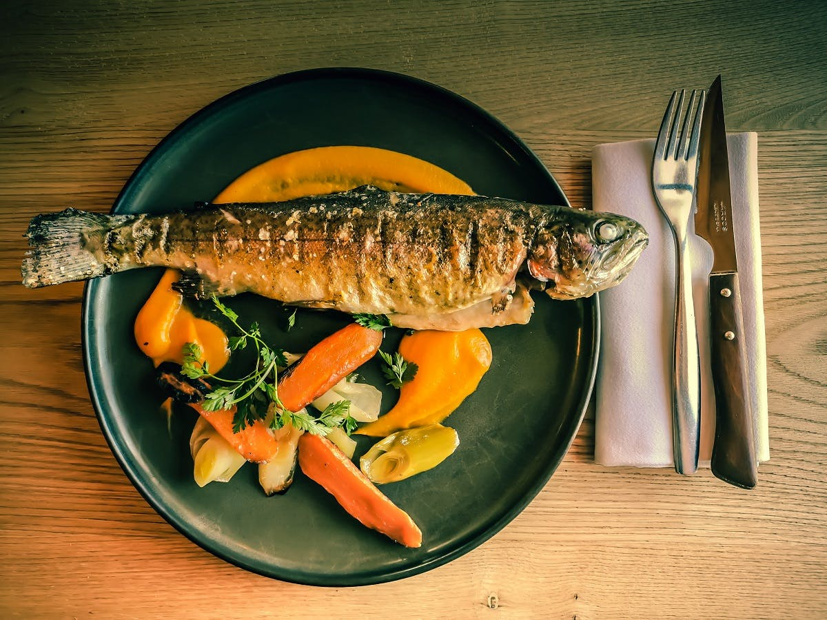 A grilled fish and colourful fresh vegetables served on a black plate