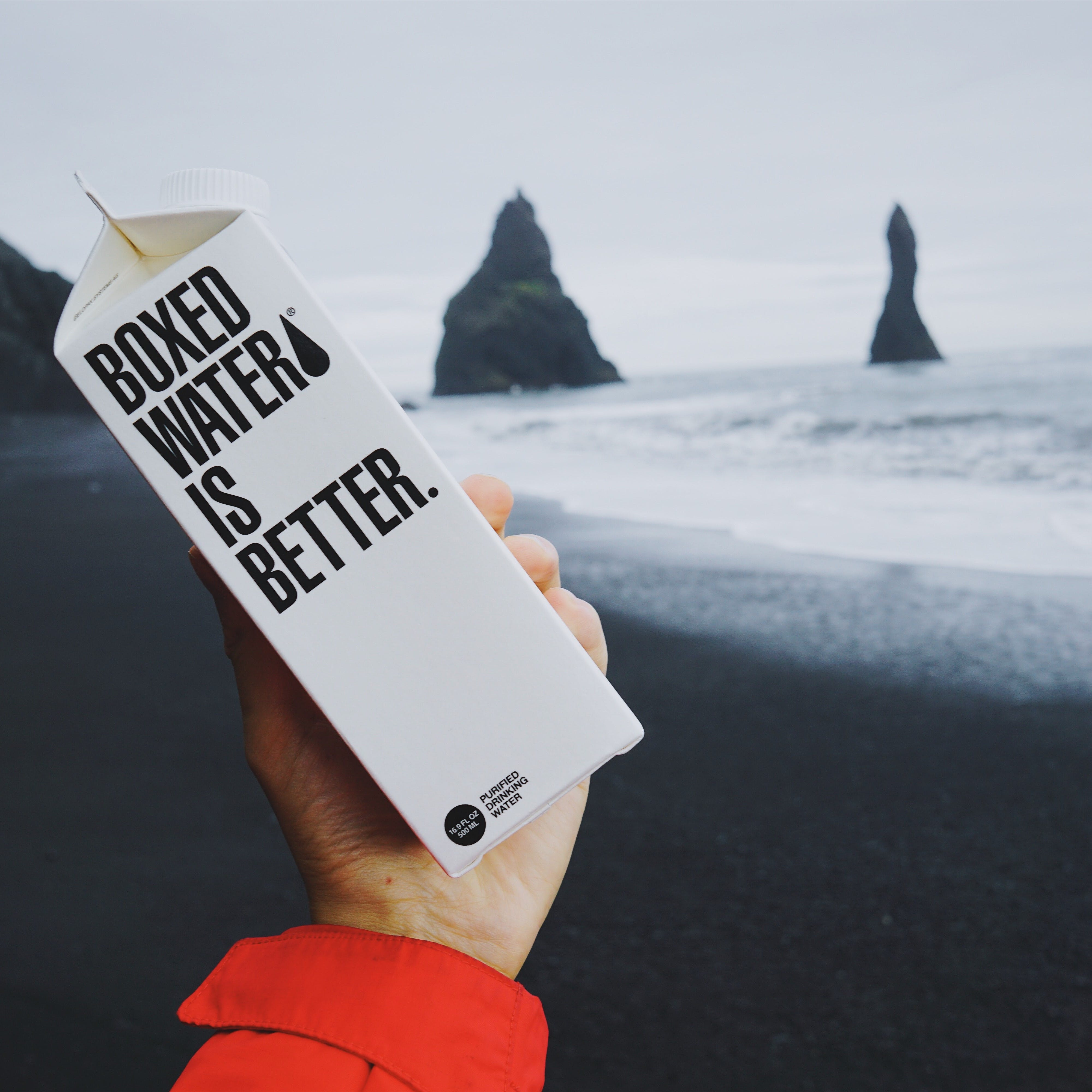 A person holding boxed water on a beach