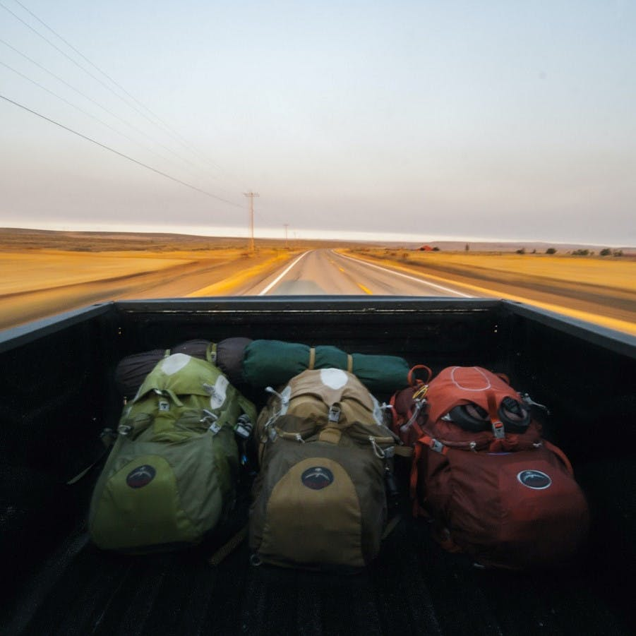 Three backpacks and camping gear in the back of a pick up. Hitchhiking is an adventurous way to travel without flying