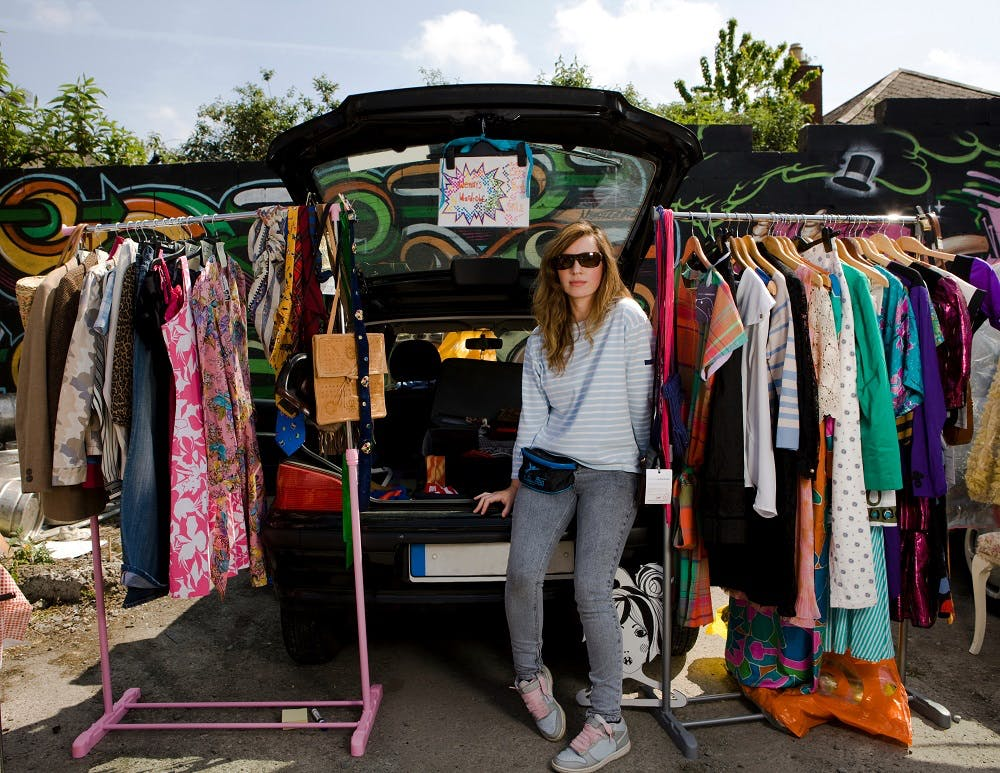 A girl getting rid of her second hand clothes at a car boot sale