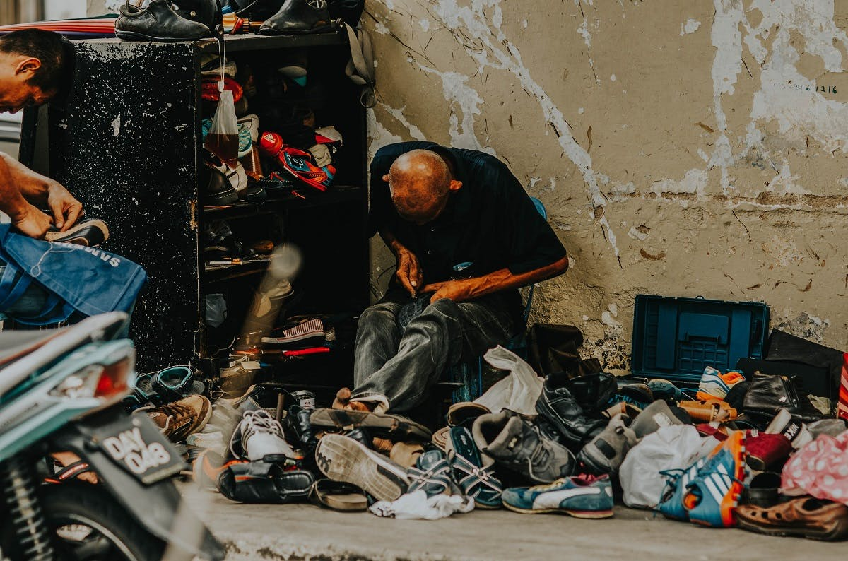 A repairing shoes on the street. Keeping your shoes and clothes in circulation longer will help you reduce your carbon footprint.